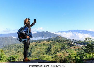 young asian women backpack tourists checking signal and map on smartphone on the mountain and mountain fog clear sky background at doi chiang mai Thailand