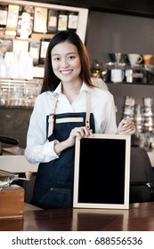 Young asian women Barista holding blank chalkboard with smiling face at cafe counter background, small business owner, food and drink industry concept
