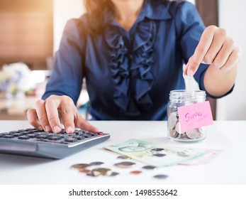 young asian women calculating and accounting income and expenses with calculator and plan future finances with savings By collecting Thai money banknote and coins.