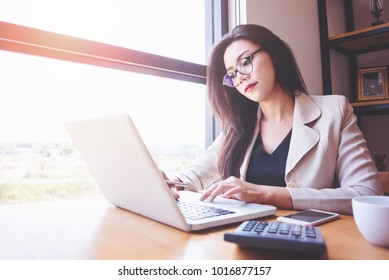Young asian women with laptop and calculator counting make notes at coffee shop,hand writing in notebook.savings finances and accountant concept.