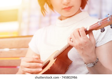 Young Asian women playing on ukulele in close up view and soft focus.