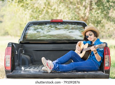 Young asian women short hair wear hat and sunglasses playing guitar ,sit on pickup truck in countryside Thailand