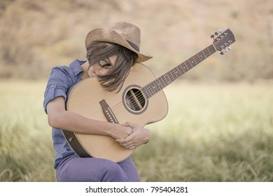 Young asian women short hair wear hat and sunglasses sit playing guitar in grass field countryside Thailand