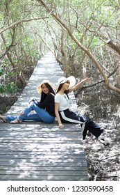 Young asian women sitting on the wooden bridge with happiness