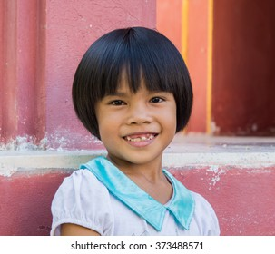 young Asian women smiles and shows the church red wall cavities