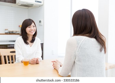 young asian women talking in the kitchen