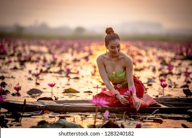 Young Asian women in Traditional dress in the boat and pink lotus flowers in the pond.Beautiful girls in traditional costume.Thai girl in retro Thai dress, Thai girl in traditional dress costume