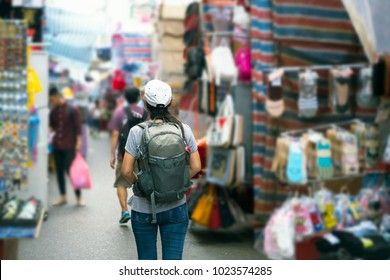 Young Asian women traveler with backpack walking market street vacation, tourism concept traveling on holidays in Hong Kong