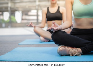 Young asian women wearing sportswear,  practicing yoga meditation with friend at outdoor, well being and wellness concept