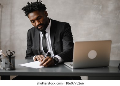 a young aspiring African-American investor works at a computer, analyzes the securities market