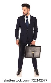 young assasin holding a gun and briefcase looks to side on white background