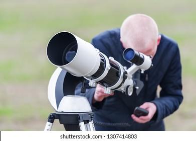 Young astronomer looking skyward through astronomical telescope