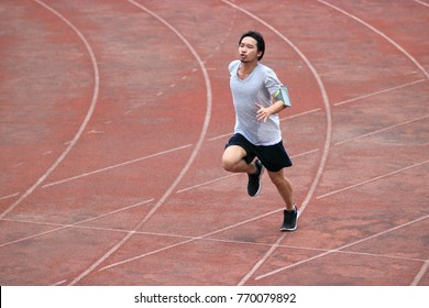 Young athlete Asian man running on racetrack in stadium. Healthy active lifestyle concept.