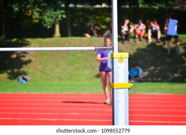 A young athlete in the background prepares for the high jump competition: in the foreground the measure with the pole.