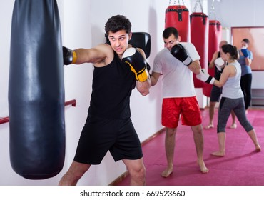 Young athlete is beating a boxing bag in the boxing hall.