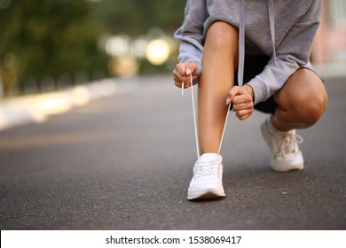 young athlete. beautiful girl athlete tying shoelaces on sneakers. beautiful girl athlete sitting tying shoelaces on white sneakers. Healthy lifestyle concept.