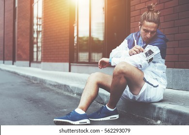 Young athlete in blue windrunner sitting on the street adjusting running program for his morning workout using mobile phone in armband