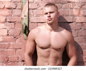 Young athlete bodybuilder man near brick wall
