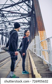 Young athlete couple stretching outdoors.
