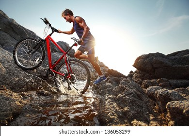 Young athlete crossing water barrier with bicycle