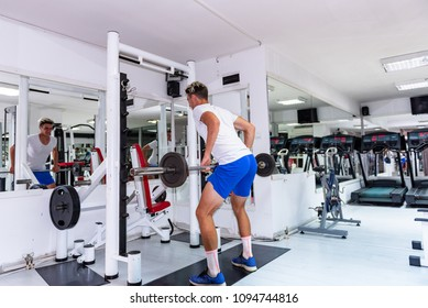 Young athlete doing exercise for back with barbell. Handsome young man doing heavy weight exercise for back, rowing