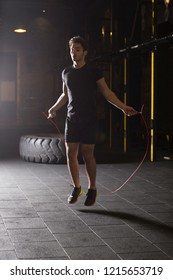 Young athlete doing jump rope exercises at the gym. Dark photography concept with copy space text area.