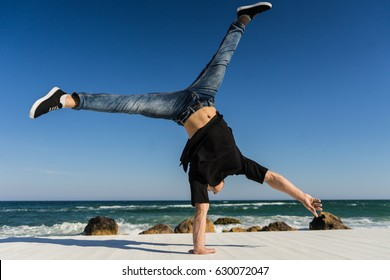 Young Athlete doing one arm handstand on the beach. Street workout. break dancer man