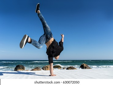 Young Athlete doing one arm handstand on the beach. Street workout. break dancer man in action