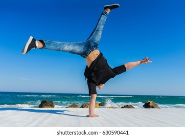 Young Athlete doing one arm handstand on the beach. Street workout. break dancer man. Freedom comcept
