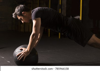 Young athlete doing pushups on a medicine ball