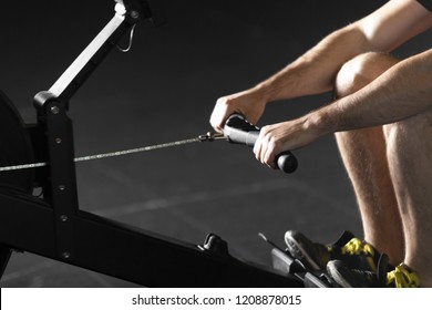 Young athlete doing rowing exercises in dark concept gym.