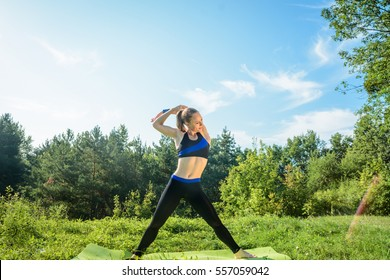 Young athlete engaged in a park. Stretching. Pilatess. Yoga. Healthy lifestyle. Mock up
