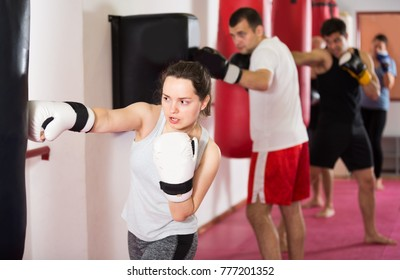 Young athlete female is beating a boxing bag in the boxing hall.