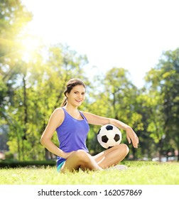 Young athlete female sitting on a green grass and holding a soccer ball in a park, shot with a tilt and shift lens