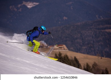 young athlete freestyle Skier having fun while running downhill in beautiful Alpine landscape on sunny day during winter season