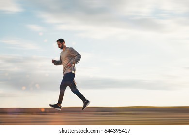 Young athlete in headphones and sports clothes and sneakers runs in the park. Lubricated background. Motion blur