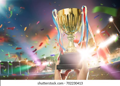Young athlete holding up a gold trophy cup with space ready for your trophy design. Grand stadium celebration with spotlight , flare and confetti ..