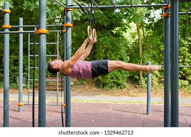 Young athlete in horizontal position hanging on rings doing exercises during calisthenic training outdoors in park on summer.