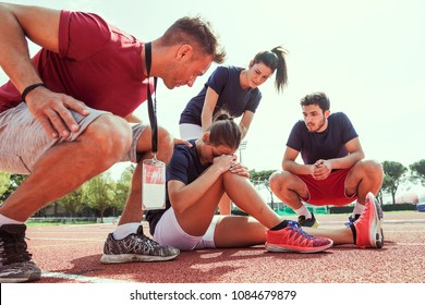 young athlete injured to knee on the track while being helped by his coach and his teammates