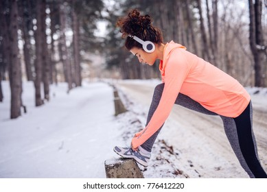 Young athlete lacing her shoes outdoors