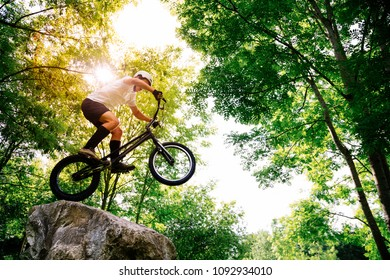 Young athlete making tricks on his trial bicycle up in a rock in the forest