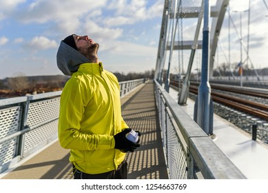 Young athlete man drinking water - dehydrating during exercise outdoors.