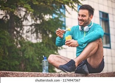 Young athlete man eating fruit after exercising.
