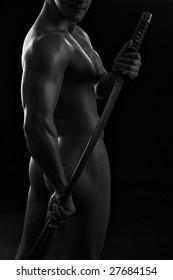 Young athlete man holding samurai sword over dark background