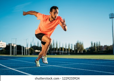 Young athlete man starting to run in a start position in a race. Start stride