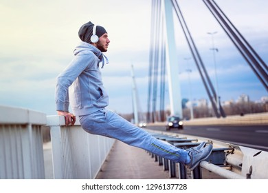 Young athlete man stretching his muscles before running on bridge. Exercising, Jogging, Sport, extreme.