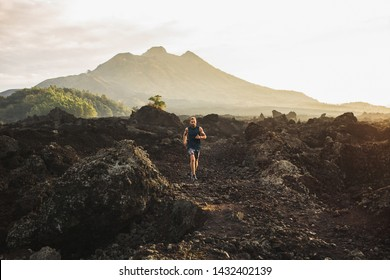 Young athlete man trail running in mountains in the morning. Amazing volcanic landscape of Bali mount Batur on background. Healthy lifestyle concept.