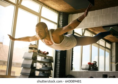 Young athlete man workout in healthy club. Athlete levitates above ground during training.