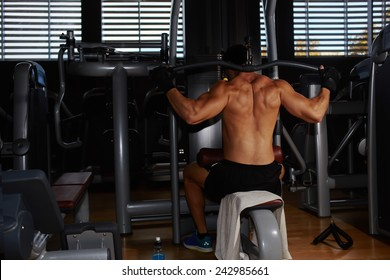 Young athlete with muscular body working out on pull down machine at gym