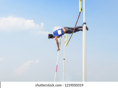 young athlete pole vault pole jumping competition over bar in to the sky at stadium
